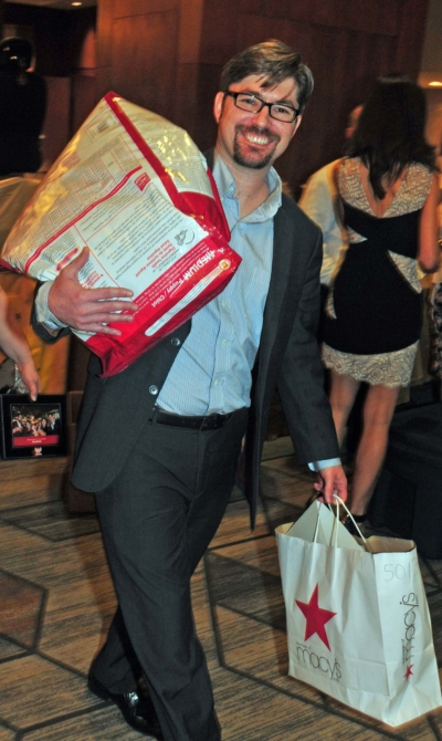 man walking away with his silent auction items